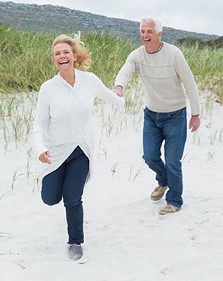 mature-couple-running-beach